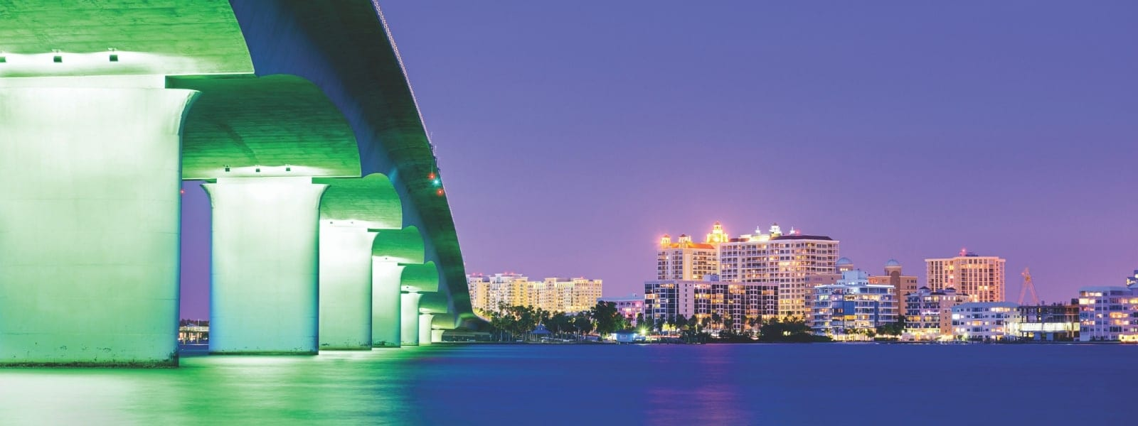 The Sarasota bay at sunset lit up with the bottom of the bridge on the left and the city lights straight ahead