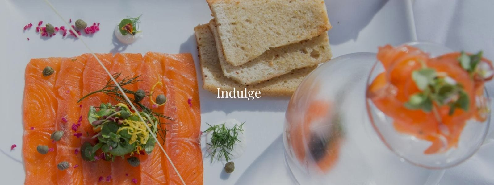 Salmon and bread displayed on a plate with the word Indulge