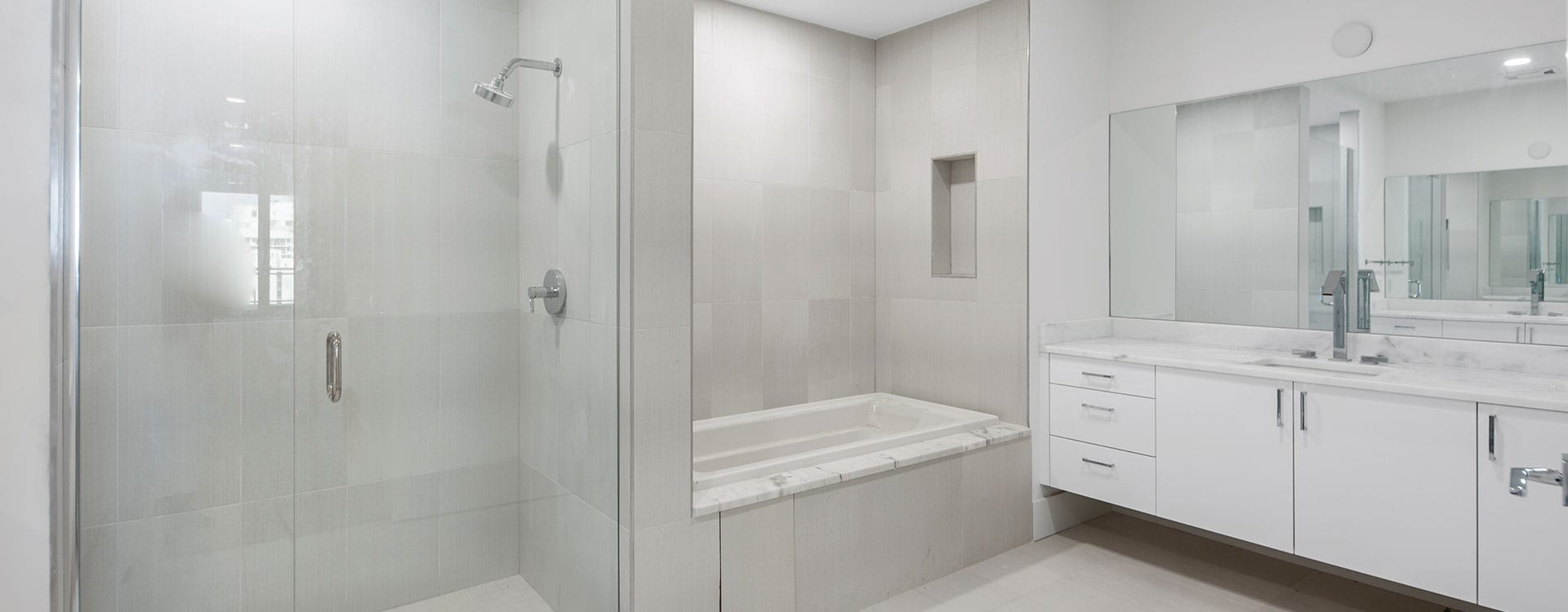 BLVD Sarasota Residence 1102 Bathroom with a soaking tub, walk-in shower and dual sinks